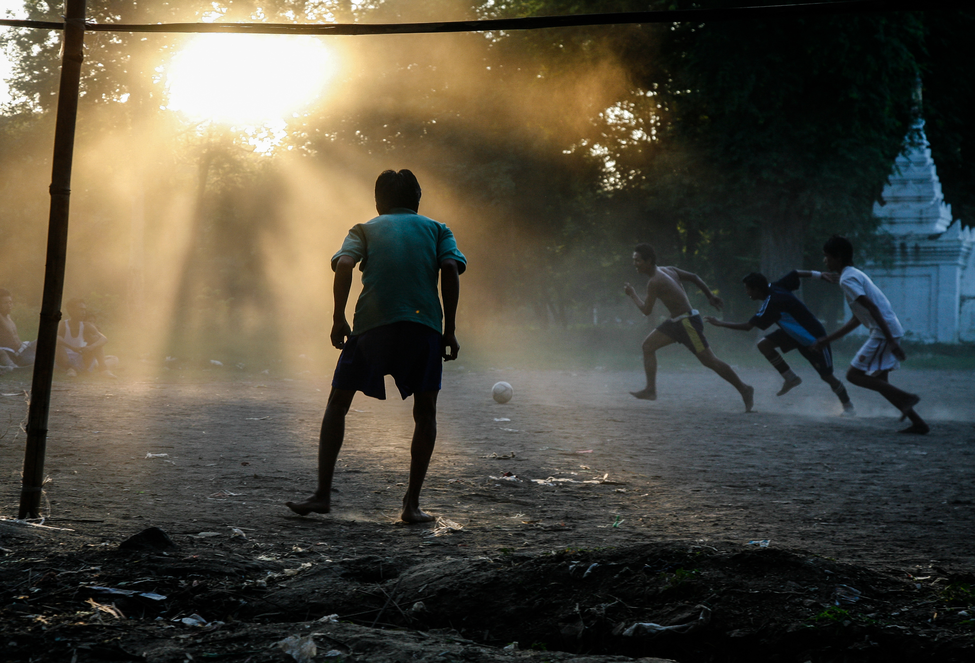 Boys playing football in the dust